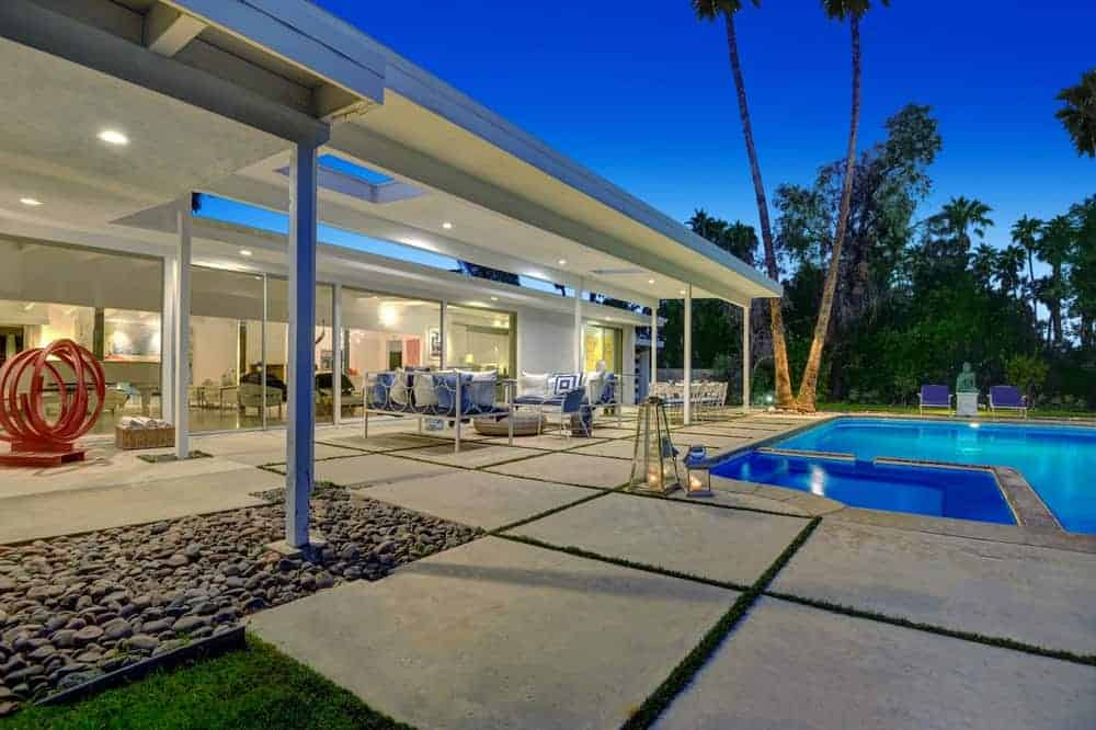 This is the view of the covered patio beside the poolside area. This showcases the beautiful concrete slab walkways that transition to pebbled grounds and the grass lawn.
