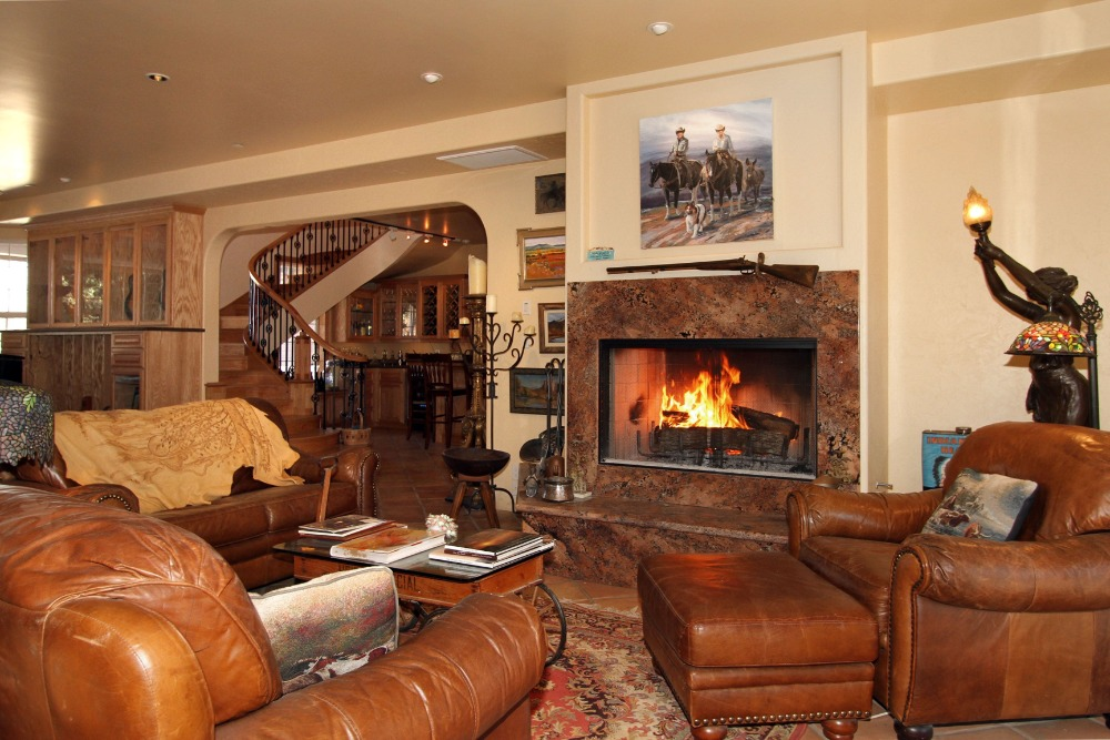 A closer look at the formal living room's brown leather sofa set along with a styish fireplace. Images courtesy of Toptenrealestatedeals.com.