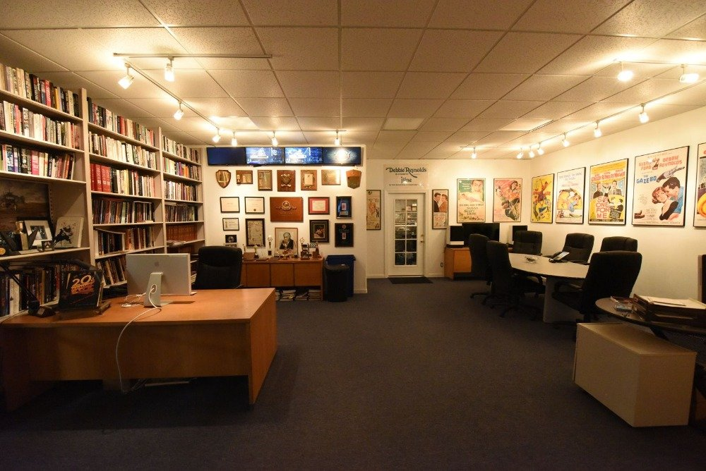 Large home office with an office desk, a study desk and a multi-use table on the side. The room has built-in shelving as well, filled with books. Images courtesy of Toptenrealestatedeals.com.