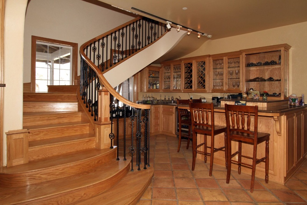 A bar area situated under the home's curved staircase. It has a small bar counter with three bar stools. Images courtesy of Toptenrealestatedeals.com.