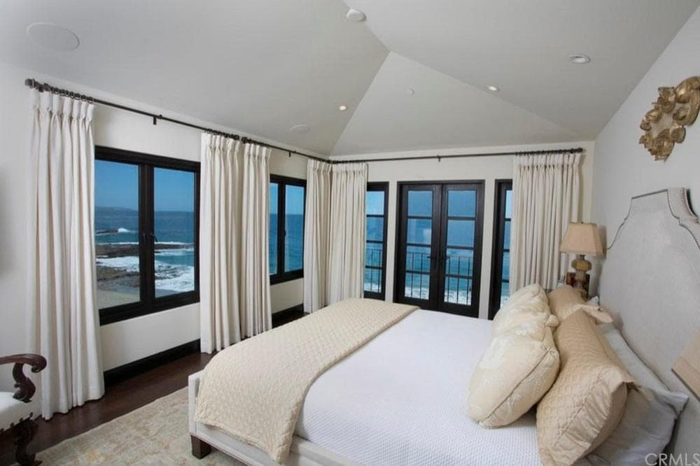 This bedroom has a large bed that has a gray cushioned headboard. this is then complemented by the row of large windows and glass doors that give a sweeping view of the ocean beyond. Images courtesy of Toptenrealestatedeals.com.