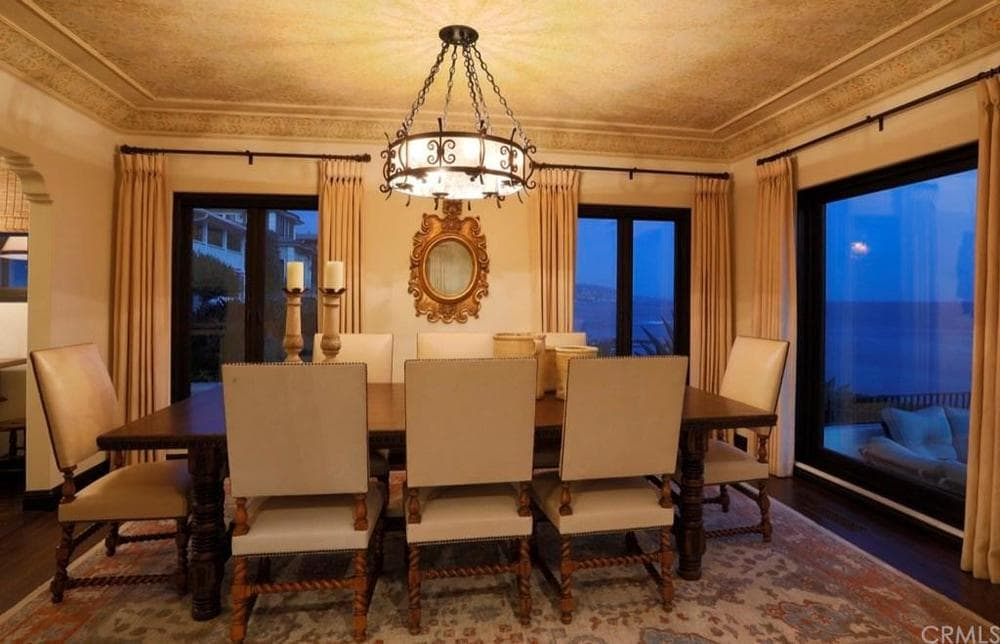 This charming dining room glows warm with the drum chandelier hanging over the rectangular dark wooden dining table surrounded by beige cushioned chairs that match the walls. Images courtesy of Toptenrealestatedeals.com.