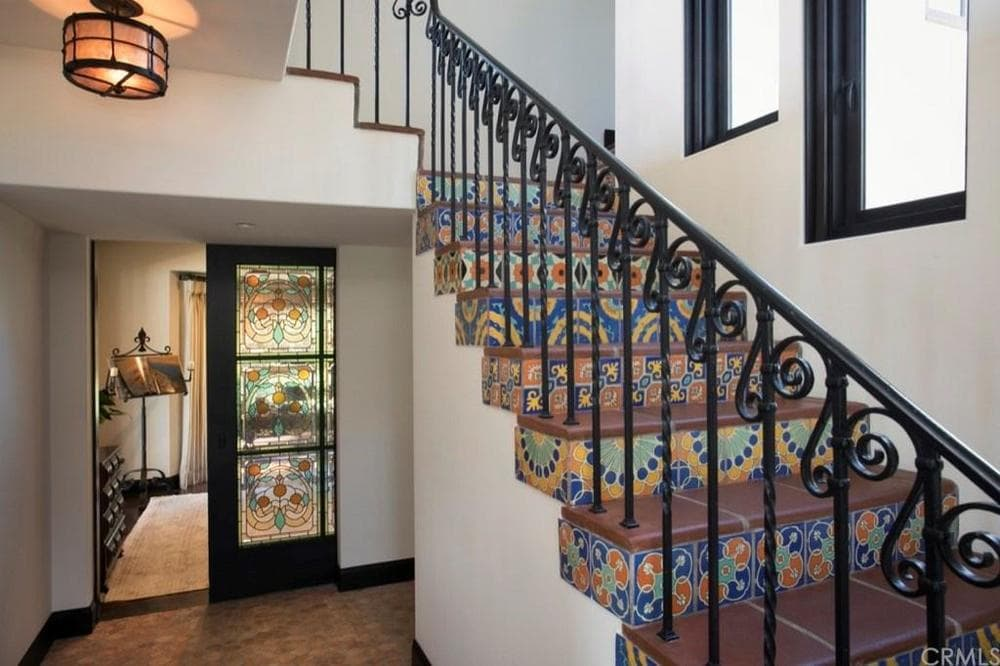 The staircase stands out in this foyer. It has colorful patterned tiles on its steps as well as intricate wrought iron railings that stand out against the beige walls and ceiling. Images courtesy of Toptenrealestatedeals.com.