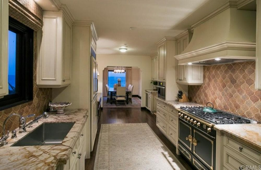 This galley kitchen has a dark hardwood flooring that is mostly covered by a beige area rug to match the beige cabinetry and the ceiling. These are complemented by the beautiful backsplash and dark iron stove-top oven. Images courtesy of Toptenrealestatedeals.com.