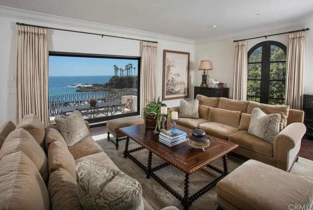 This lovely living room has a couple of comfortable beige sofas to match the beige walls and ceiling. These are then complemented by the wood-top coffee table and the beautiful ocean view outside the large glass window. Images courtesy of Toptenrealestatedeals.com.