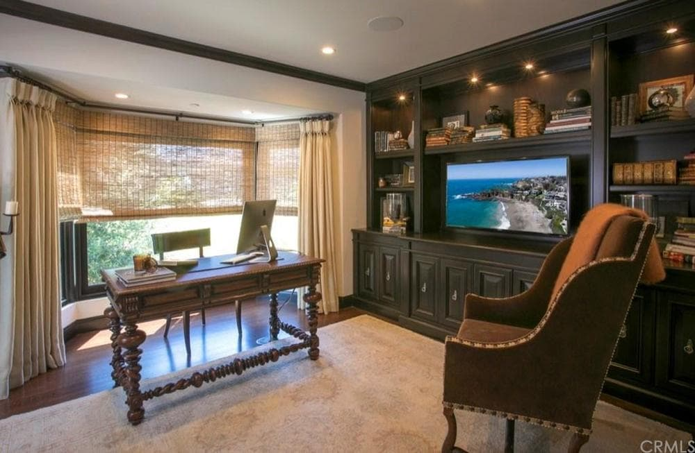 This simple yet elegant home office has a wooden desk that matches the dark wooden tone of the built-in wooden structure on the side that has cabinets, shelves and a TV. Images courtesy of Toptenrealestatedeals.com.