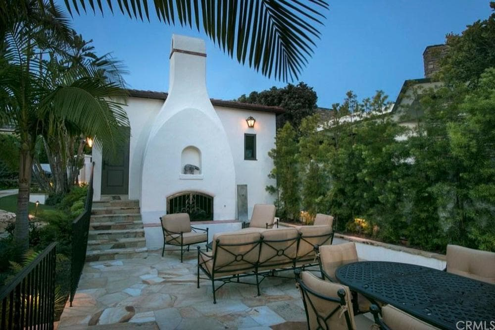 This is the relaxing and lovely patio with a cushioned wrought-iron sofa set warmed by the charming outdoor fireplace adorned with hedges on the side. Images courtesy of Toptenrealestatedeals.com.