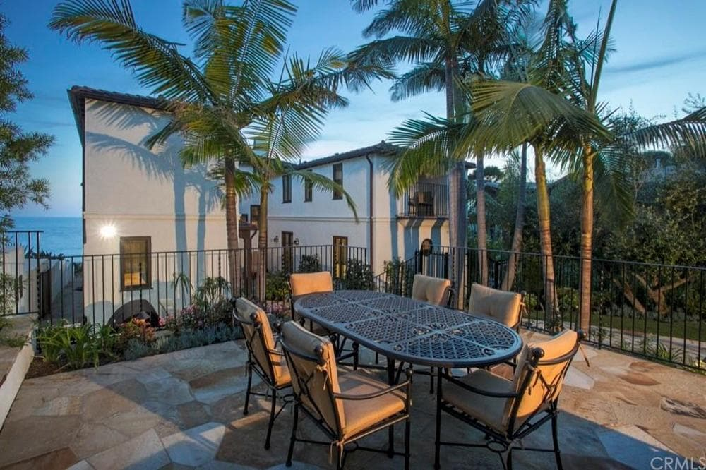 Beside the sitting area of the patio is this outdoor dining with a wrought-iron dining set that stands out against the mosaic stone flooring and the background of tall tropical trees. Images courtesy of Toptenrealestatedeals.com.