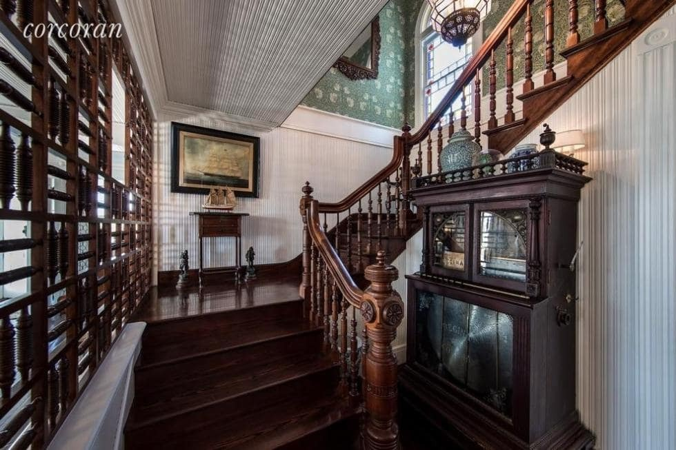 A look at the home's staircase with hardwood steps and wooden railing and handrail. Images courtesy of Toptenrealestatedeals.com.
