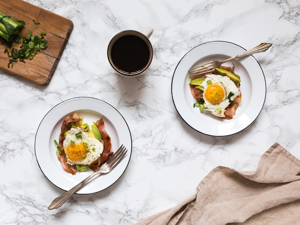 A couple of plates of eggs, bacon and avocado breakfast.