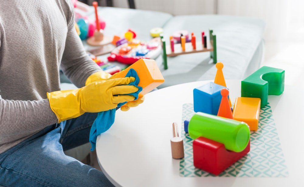 A gloved man cleaning the toys of his kids.