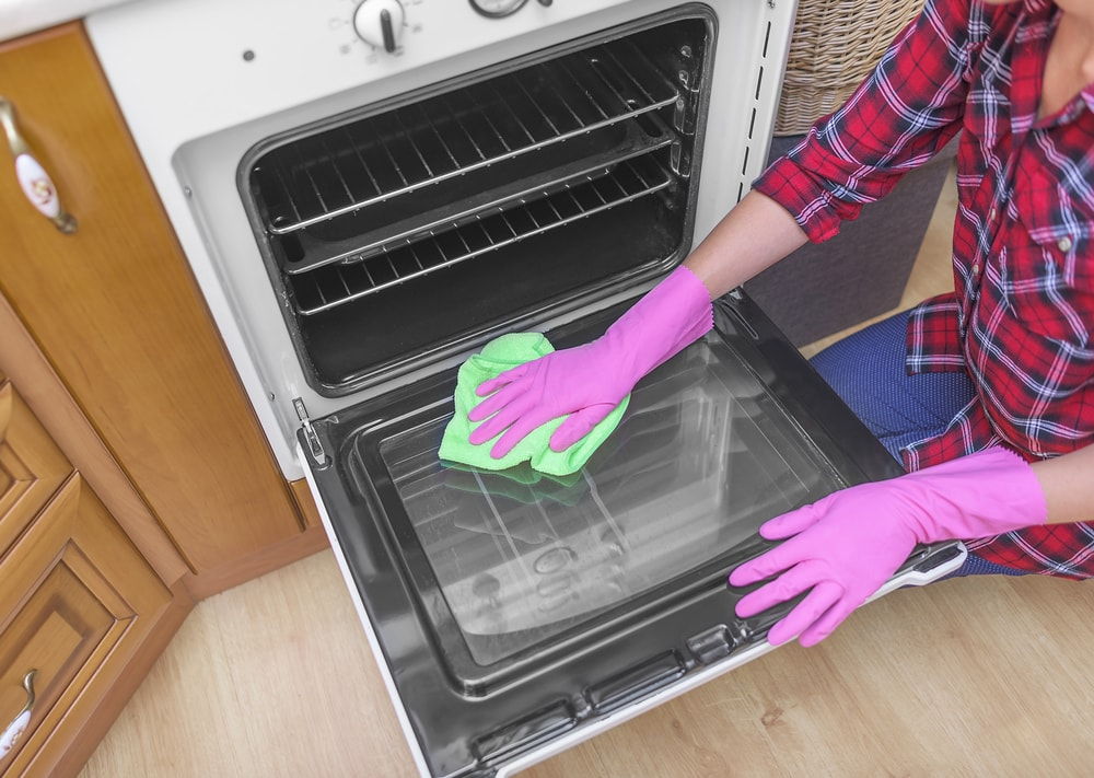 A gloved woman cleaning the oven glass door.
