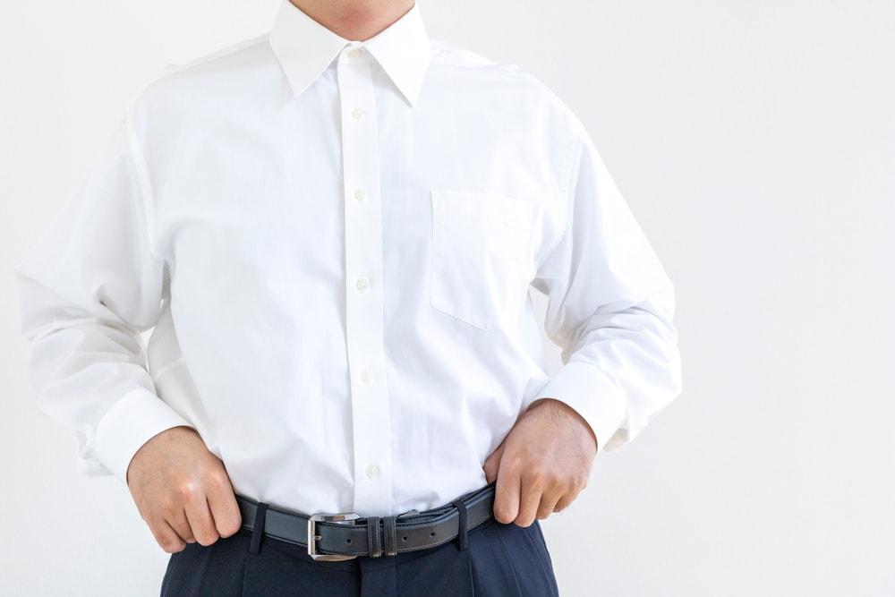 A man wearing a white button-down long sleeve shirt.
