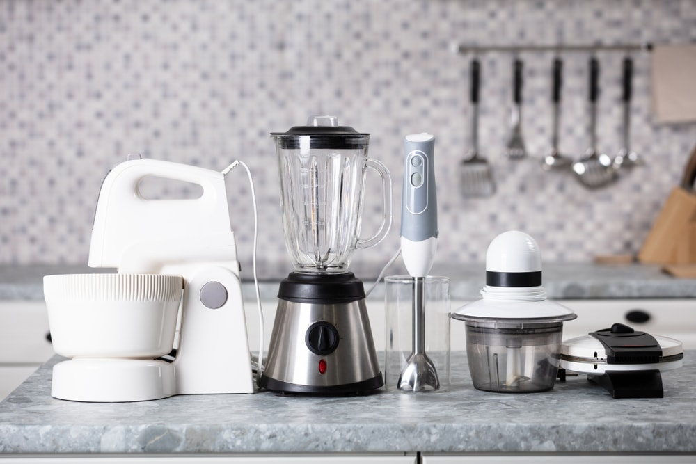 Various small kitchen appliances on the granite countertop.