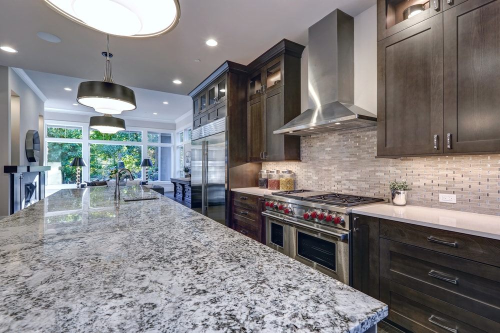 A close look at the granite countertop of a kitchen with brown cabinetry.