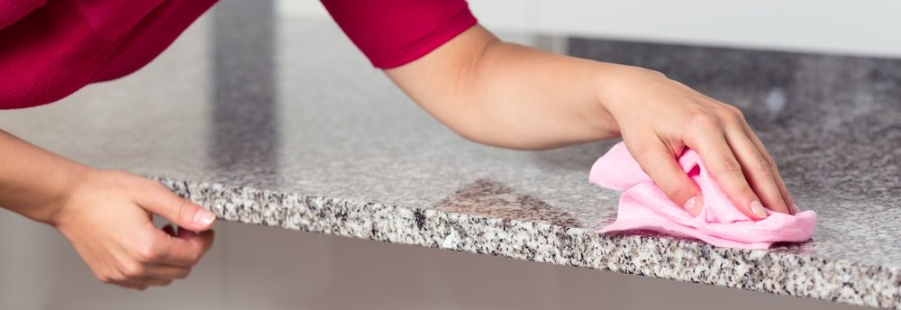A woman cleaning the granite countertop.