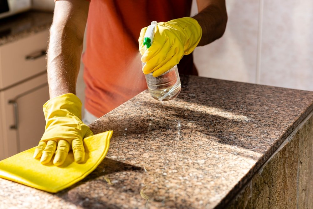 A gloved man cleaning the countertop with a spritzer and sponge.