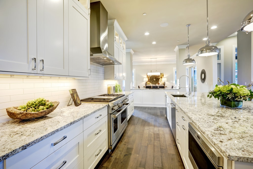 A bright galley kitchen with white granite countertops.