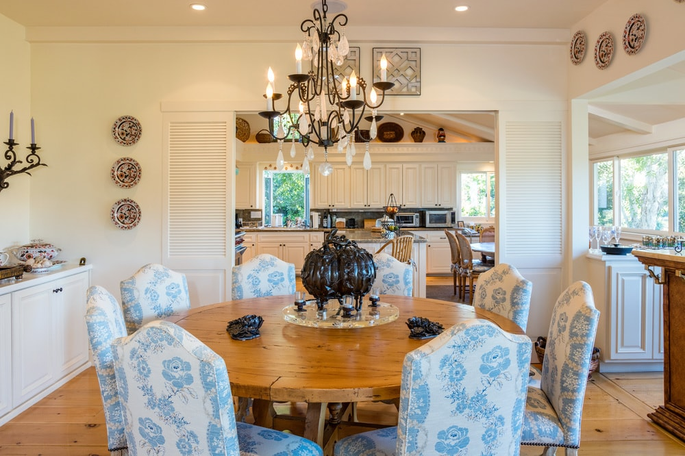 This dining room has an elegant round wooden dining table surrounded by floral dining chairs and topped with a charming chandelier. Images courtesy of Toptenrealestatedeals.com.