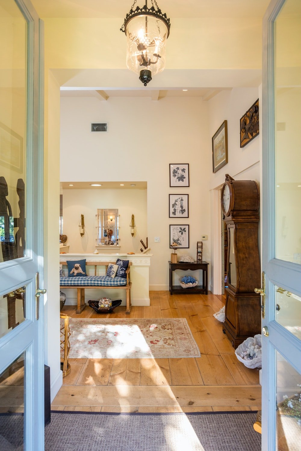 The simple and charming foyer has wooden double doors dominated by glass panels. It also has beige walls and a tall beige ceiling that hangs a simple decorative lighting over the hardwood flooring topped by a gray area rug. Images courtesy of Toptenrealestatedeals.com.