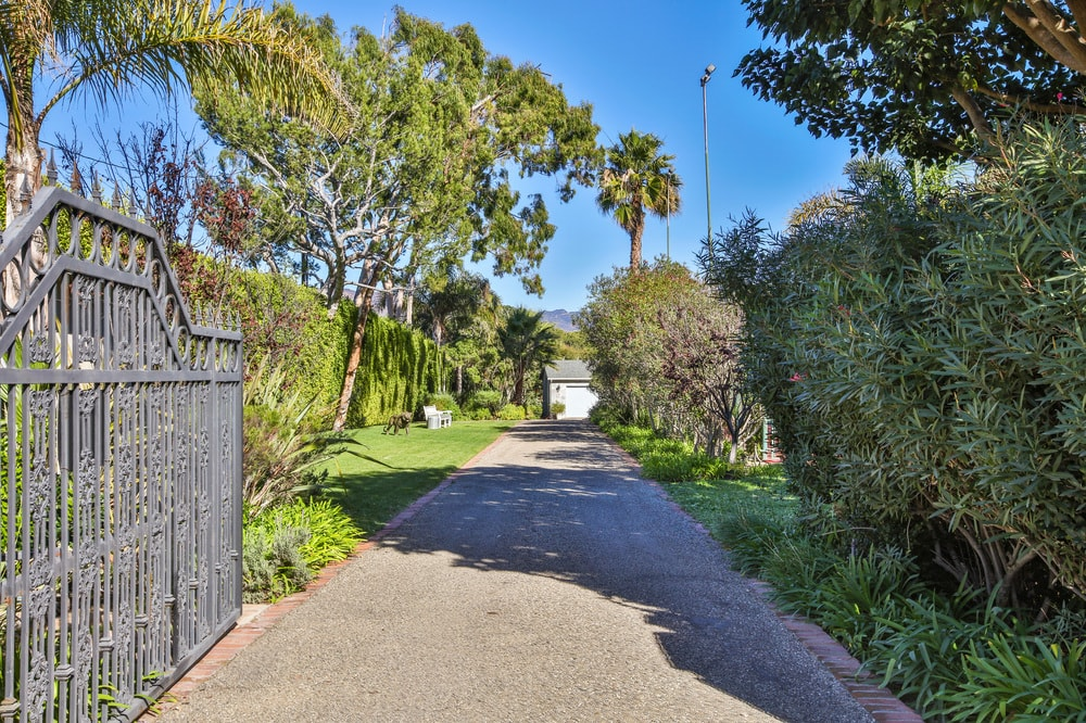 The property is protected by a large wrought-iron gate that opens up to a wide driveway flanked by grass lawns, shrubs and trees. Images courtesy of Toptenrealestatedeals.com.