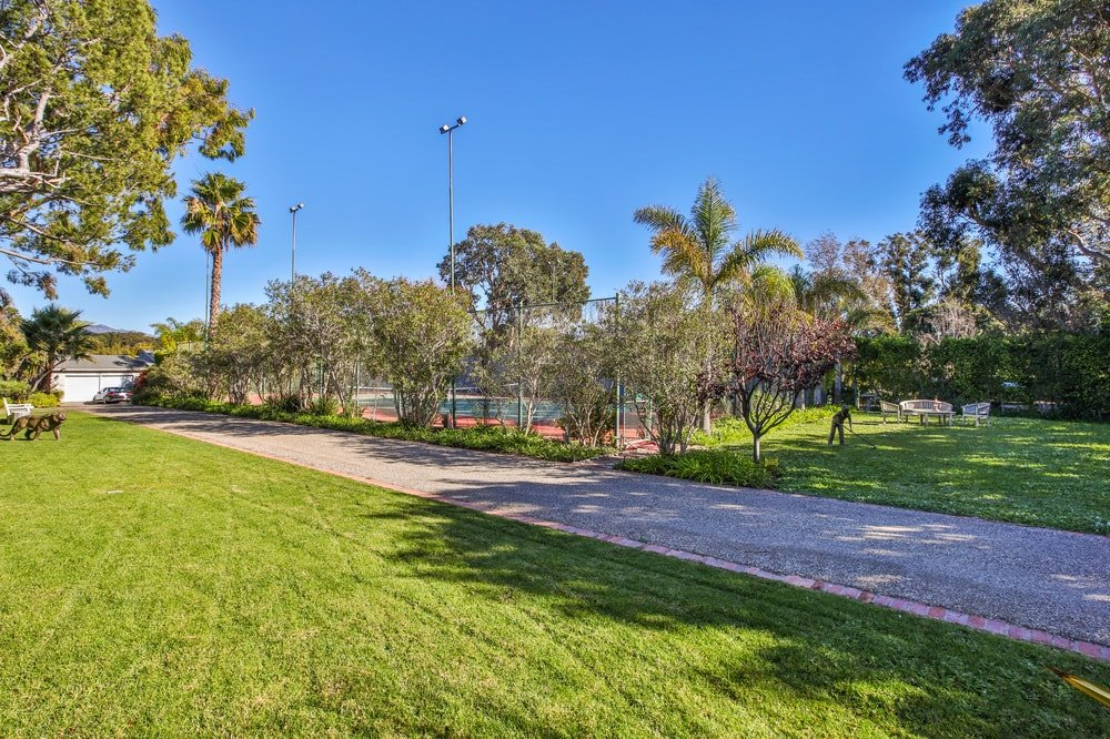 The driveway goes through a wide area of lavishly landscaped and well-maintained land filled with trees on the side of the driveway. Images courtesy of Toptenrealestatedeals.com.