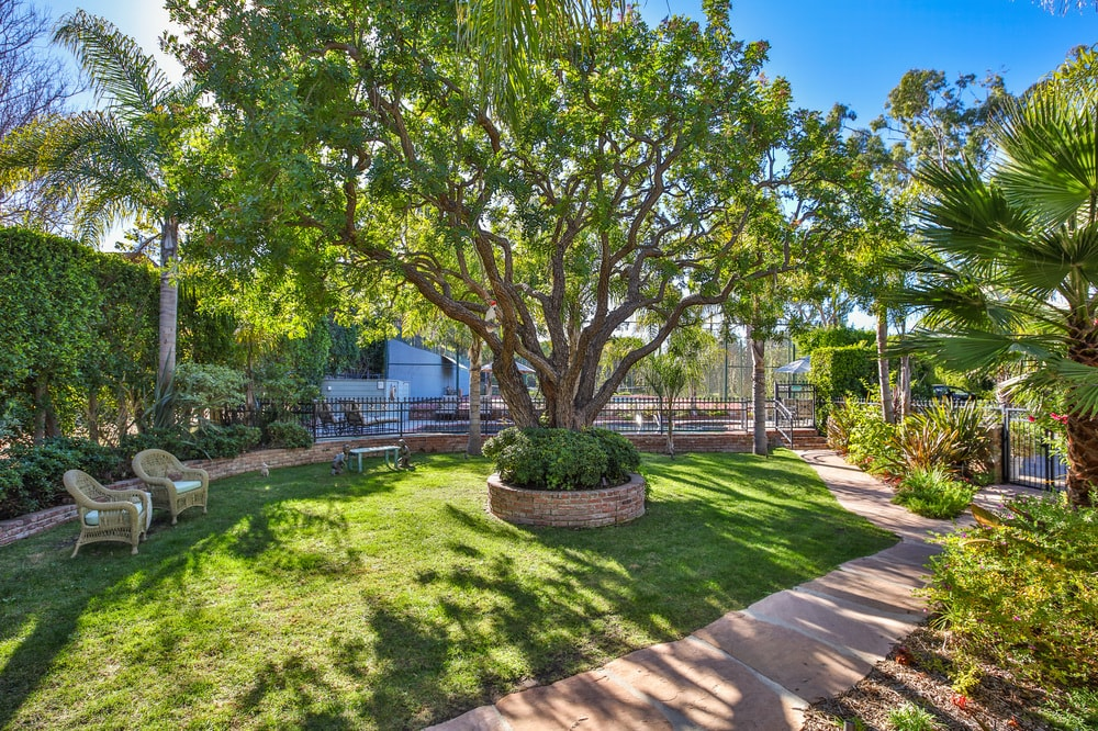 The driveway diverges to this charming walkway that is adorned with lush landscaping and shaded by the tall trees. Images courtesy of Toptenrealestatedeals.com.