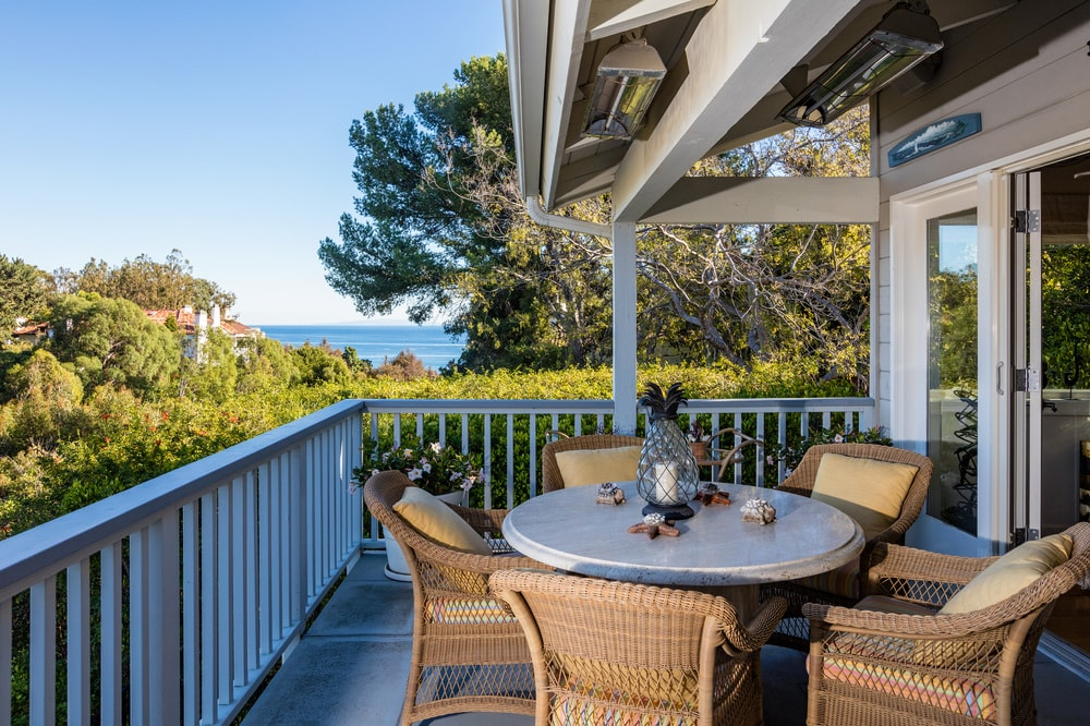 This is a close look at the outdoor dining area at the far end of the patio terrace. It has a round dining table surrounded by woven wicker chairs and has a lovely background of treetops and a glimpse of the ocean. Images courtesy of Toptenrealestatedeals.com.