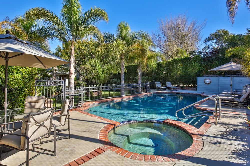 This is the large swimming pool with an attached round jacuzzi-style pool at its edge. These are lined with terracotta bricks that serve as lovely accents to complement the concrete and tall tropical trees. Images courtesy of Toptenrealestatedeals.com.