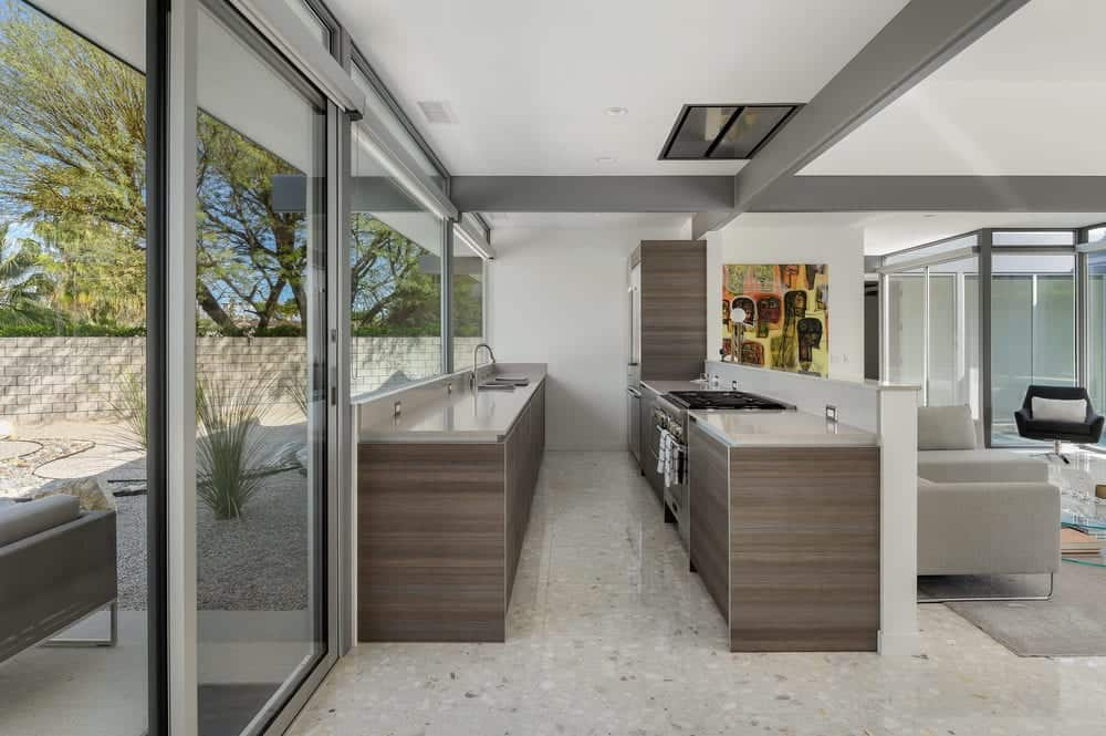 This is the long and narrow kitchen just behind the living room area. It has a large glass wall on one side to balance the narrow floor space.