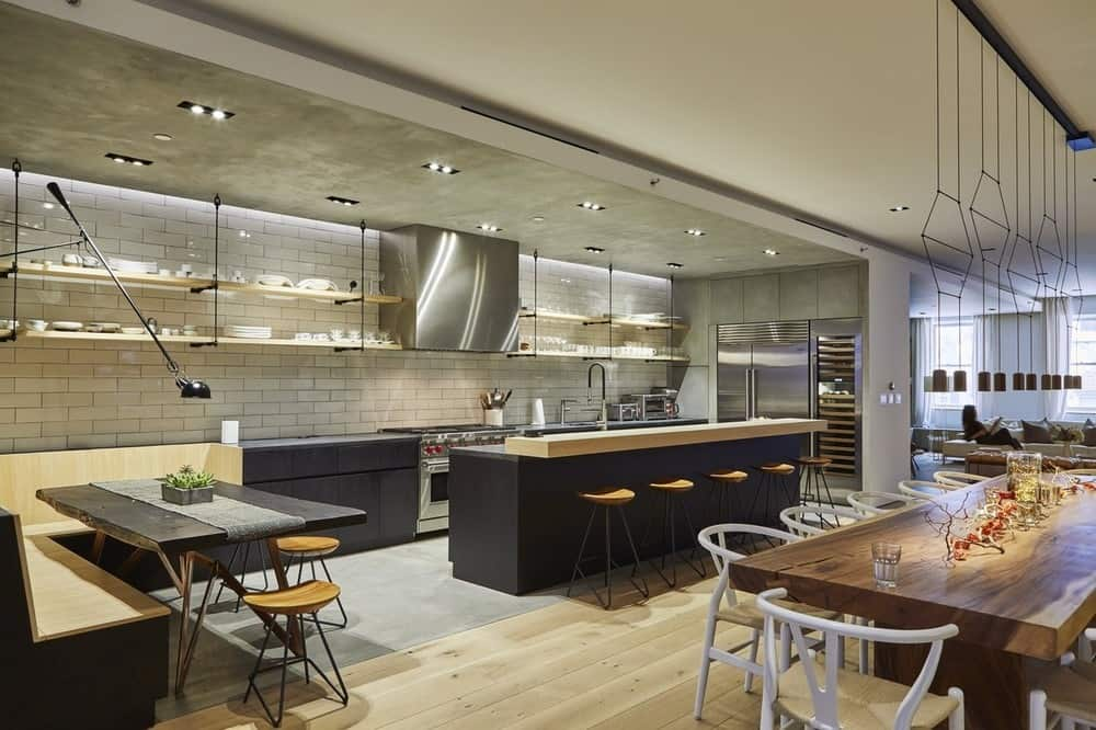 This is a beautiful kitchen with white subway tiles. Its long and narrow design affords for an informal dining area at the far end with a built-in bench.