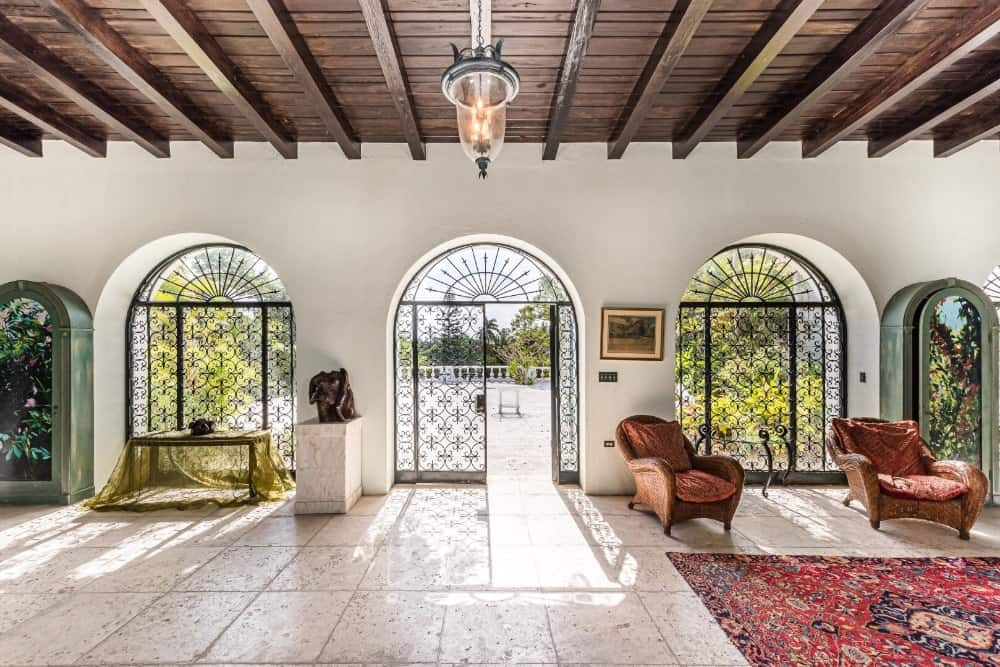 This is a spacious foyer with bright white walls complemented by the lovely arches fitted with intricate black wrought iron grills and doors.