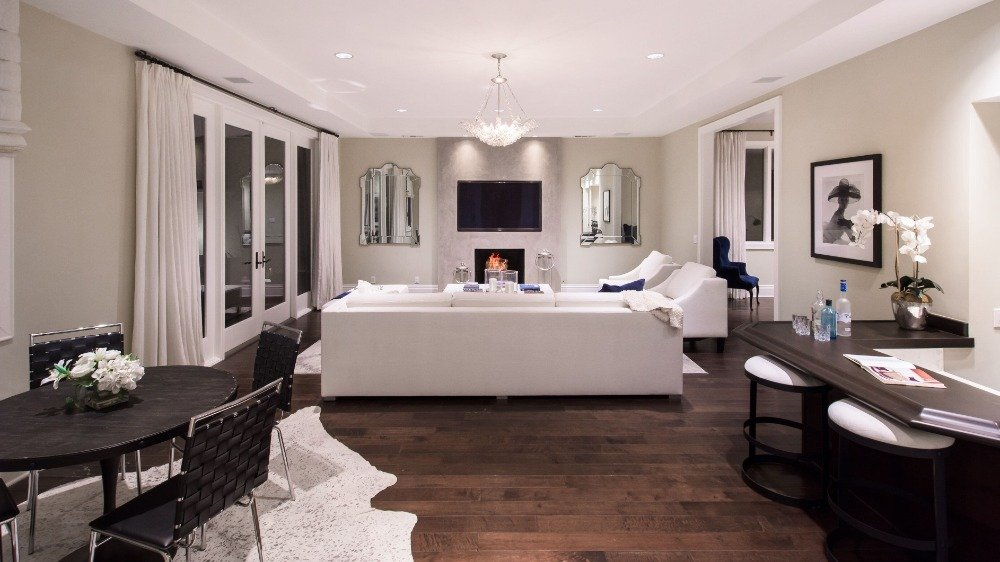 A family living space with a set of white seats, a fireplace and a large flat-screen TV on the wall. Images courtesy of Toptenrealestatedeals.com.