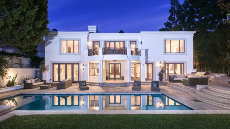 A closer look of the house featuring its white exterior and outdoor amenities such as outdoor living spaces, an outdoor kitchen and a swimming pool. Images courtesy of Toptenrealestatedeals.com.