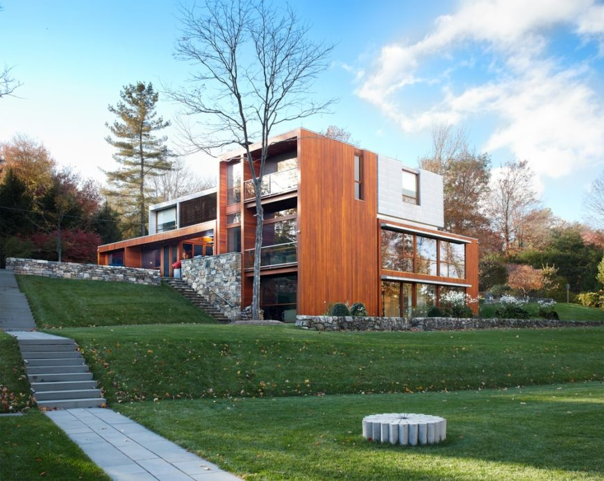 This is the view of the back of the house that has a spacious rolling lawn of grass. Here you can see the gorgeous glass walls of the house that go well with the brown tone of the exterior walls. Images courtesy of Toptenrealestatedeals.com.