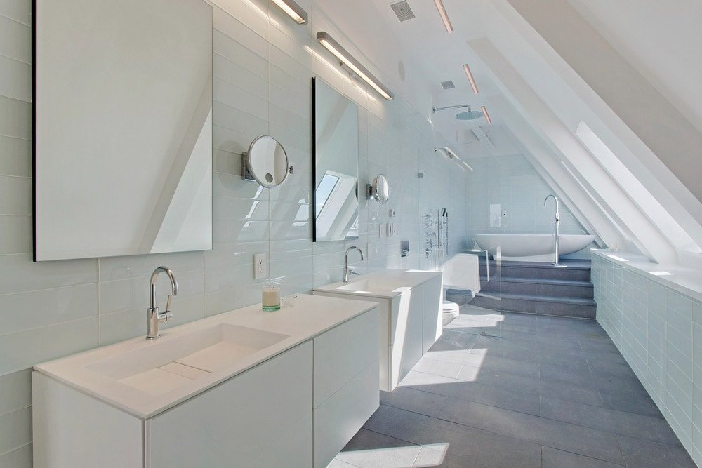 This lovely bathroom has a couple of bright vanities across from the row of window s leading to the bathtub at the far end. Images courtesy of Toptenrealestatedeals.com.