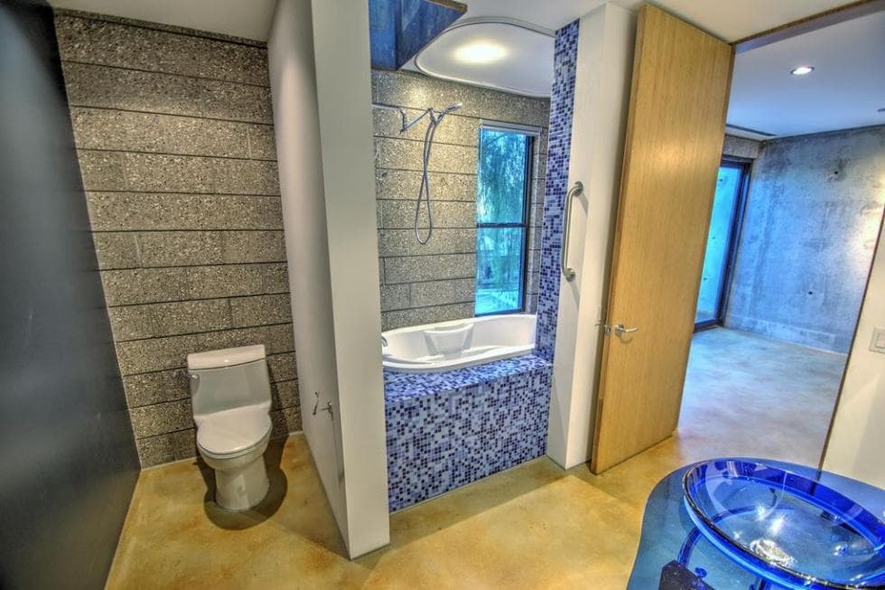 This bathroom has a toilet placed at the corner with a concrete wall separating it from the bathtub that is adorned with beautiful blue and white tiles that stand out against the light beige tone of the floor. Images courtesy of Toptenrealestatedeals.com.