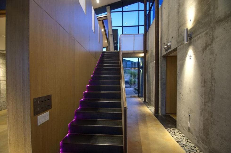 Upon entry of the house, you are welcomed by this charming foyer with a contrasting black set of stairs that stand out against the light wooden tone of the walls and floor. The sides of the stairs light up from the LED lighting that changes color. Images courtesy of Toptenrealestatedeals.com.