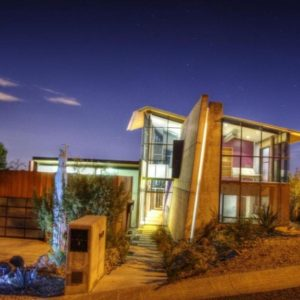 This front view of the gorgeous house makes you appreciate the amazing ingenuity of its construction. Here you can see the five-degree tilt of the concrete wall support and the surrounding glass walls that glow warmly. Images courtesy of Toptenrealestatedeals.com.