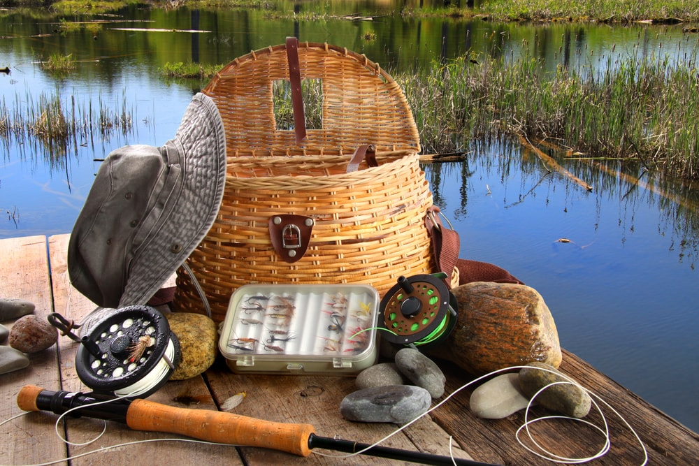 Fishing rod, hat, wicker basket, and rocks on a deck by the pond.