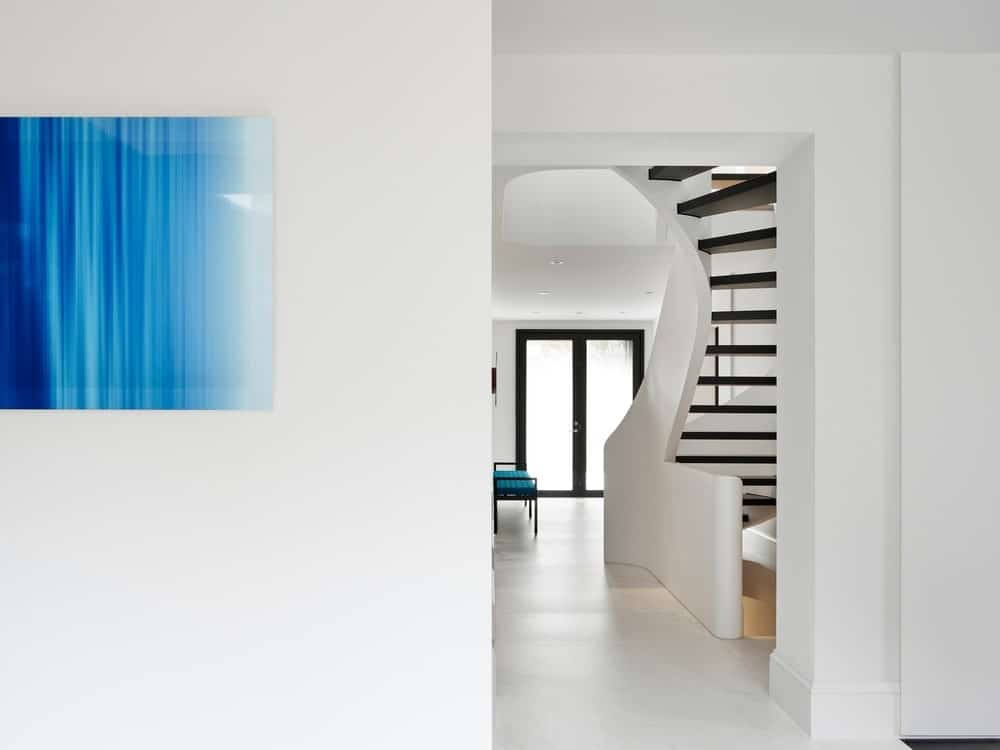This is a view of the bright and white foyer from the hallway. This simple and minimalist foyer has a glass door with black frames to match the steps of the modern spiral staircase. These elements stand out against the white walls, floor and ceiling.