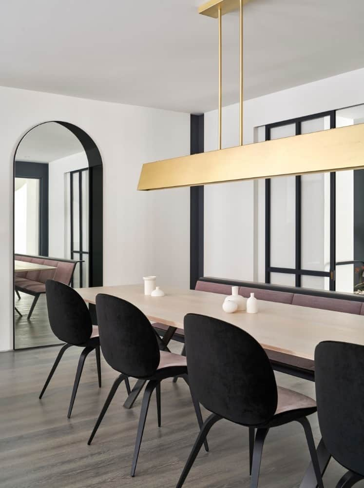 This is a close look at the simple yet elegant dining area with a large rectangular dining table paired with black chairs that match the accents on the white walls and the frames of the windows behind the long cushioned bench.