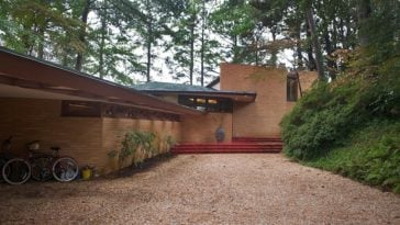 This is the pebbled walkway and driveway that leads to the main entrance and garage entrance of the house that is surrounded by mature tall trees and lush shrubs. Images courtesy of Toptenrealestatedeals.com.