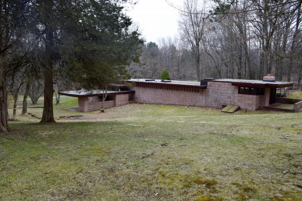 This is the view of the back of the house showing its concrete walls and surrounding lush landscape of tall trees and grass. Images courtesy of Toptenrealestatedeals.com.