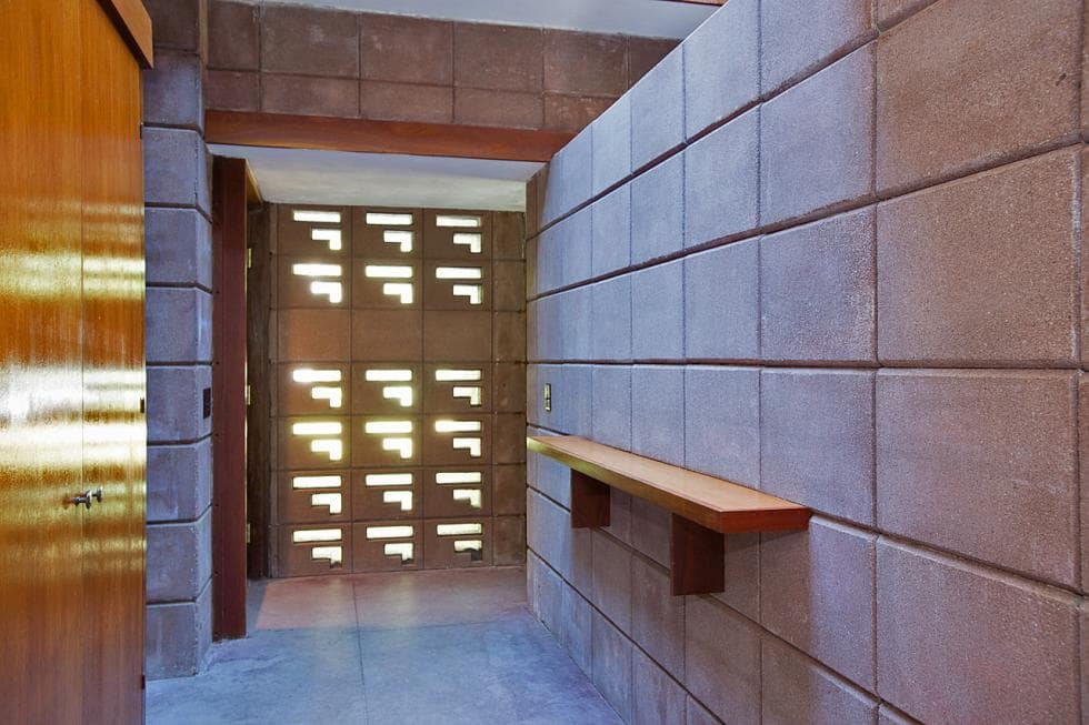 This is the simple and lovely foyer with concrete walls, a wooden floating shelf serving as a console table and patterns on the walls that bring in natural lighting. Images courtesy of Toptenrealestatedeals.com.