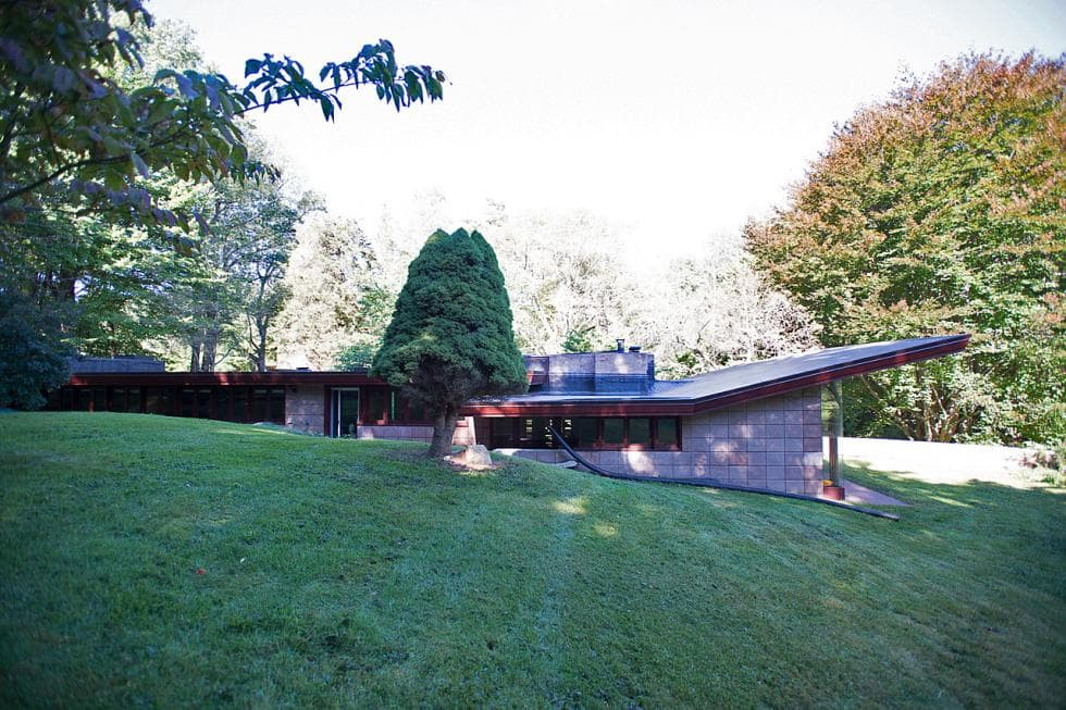 This is the front of the house. Here you can see that the structure is embedded into the elevation of the land for added insulation. It is surrounded by lush grass lawns and tall trees. Images courtesy of Toptenrealestatedeals.com.