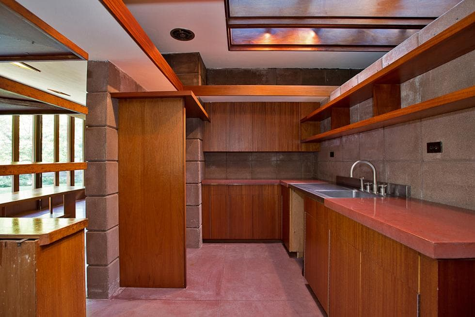The lovely kitchen has consistent wooden elements on its cabinetry and floating shelves. These ar complemented by the concrete walls and flooring tiles. Images courtesy of Toptenrealestatedeals.com.