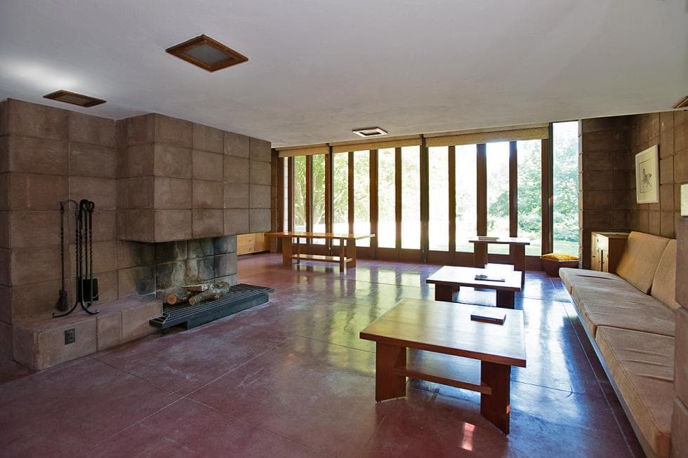 This is the spacious and airy living room with built-in cushioned seats paired with wooden coffee tables across from the large concrete fireplace. On the far side, you can see the dining area with a wooden table and wooden benches by the glass wall. Images courtesy of Toptenrealestatedeals.com.