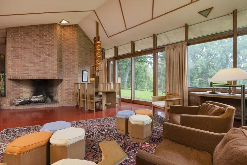 This view of the great room shows more of the beautiful large fireplace across from the living room' armchairs and ottomans. Images courtesy of Toptenrealestatedeals.com.
