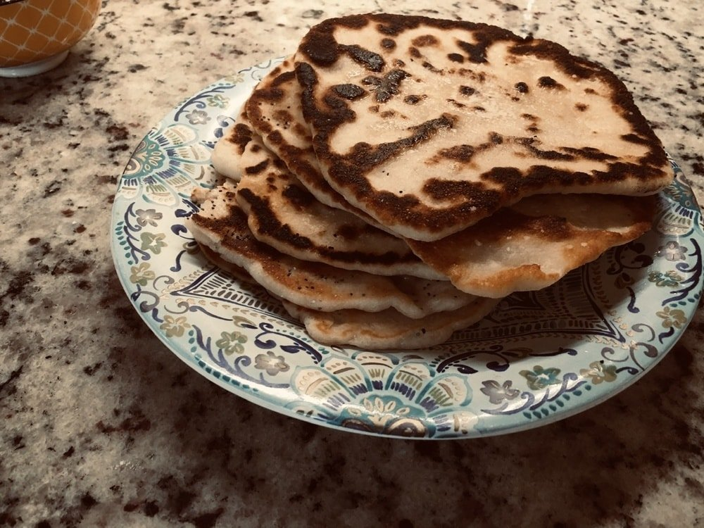 A stack of freshly cooked naan flatbread.